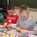 Keyton Wilson and Brarten Stegbauer work on building cars for the lego brick model of Continental.
