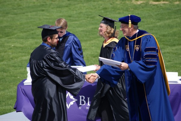 Brent Schroeder receiving his diploma from Bluffton University.