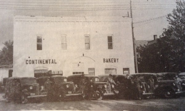 Gus Schuette and his fleet of bakery trucks and drivers in front of the Continental Bakery.